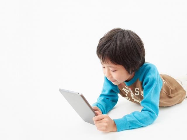 タブレットでYouTubeを見ている子供