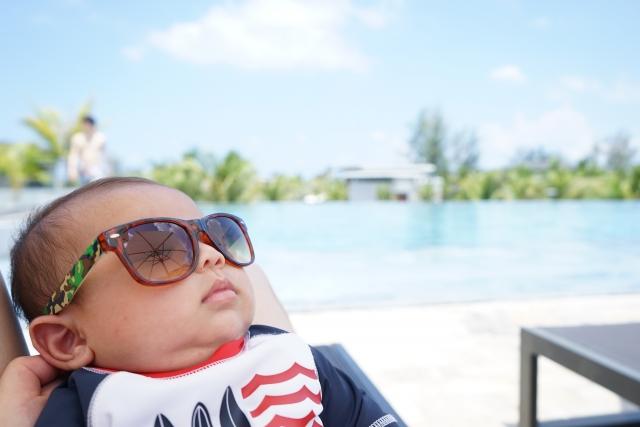 プールサイドにいるサングラスをしている赤ちゃん