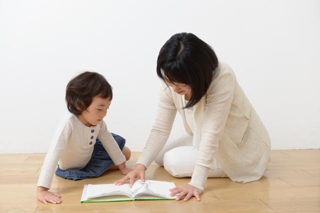 子供に絵本の読み聞かせをしているお母さん